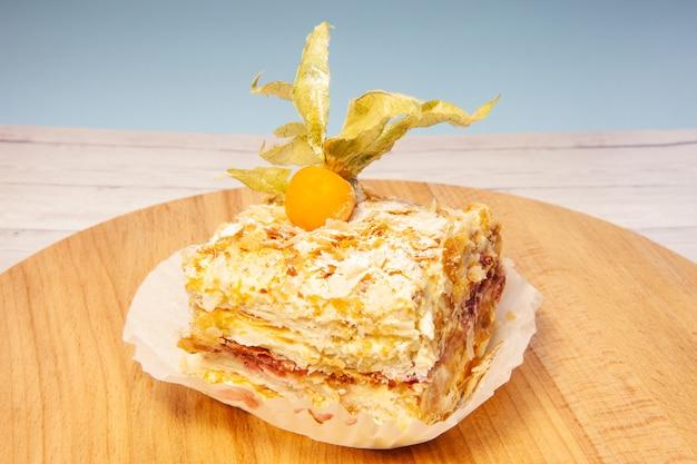 Torta acodada con la rebanada de la crema de la vainilla de napoleon en fondo de madera