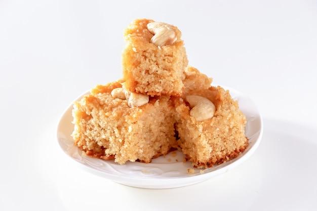 La torta árabe tradicional de la sémola de basbousa o del namoora con los anacardos y el jarabe aísla el fondo blanco foco selectivo.