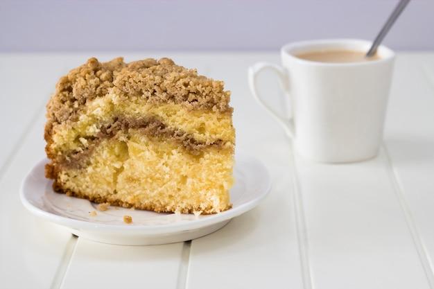 Torta de café de la migaja de la canela y taza de té en el fondo blanco