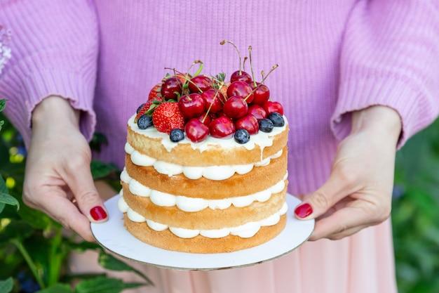 Torta casera de galletas de verano con crema y bayas frescas en manos de la mujer en el jardín