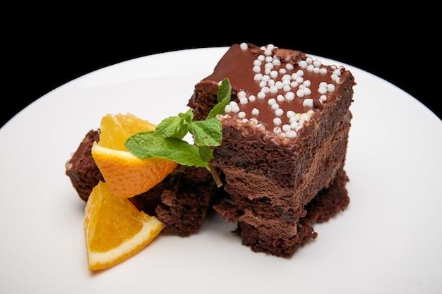 Torta de chocolate con la naranja en un plato blanco.