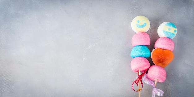 La torta colorida de las melcochas hace estallar en los palillos de madera con las caras sonrientes junto.