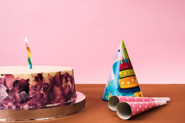 Torta de cumpleaños decorativa con los sopladores del sombrero y del cuerno del partido en el escritorio contra fondo rosado