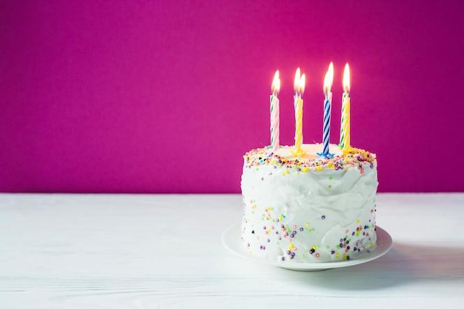 Torta de cumpleaños con velas en la placa