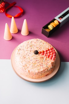 Torta deliciosa con los conos y los macarrones de las galletas en el fondo rosado y blanco