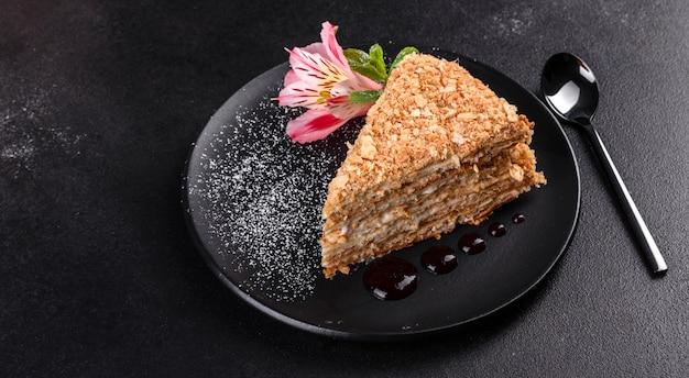 Torta deliciosa fresca napoleon con crema en un fondo oscuro. pastel compuesto por cordones y crema