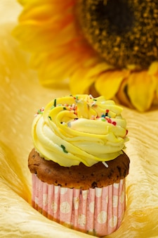 Torta deliciosa de la taza de la vainilla con la formación de hielo amarilla
