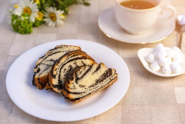 Torta dulce de semillas de amapola en un plato, en una mesa y una taza de té