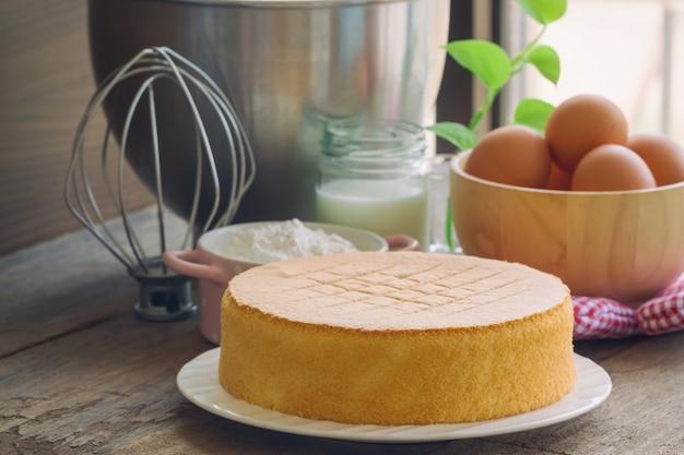 Torta de esponja hecha en casa en la placa blanca torta de esponja deliciosa suave y ligera con los ingredientes.