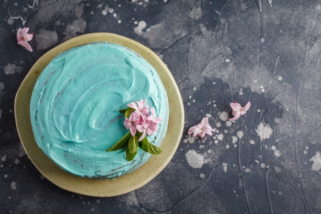 Torta con estilo azul con flores y menta. copia espacio, fondo oscuro, comida laica plana.