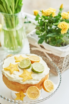 Torta con limones, limas, carambola en la mesa junto a los tulipanes.