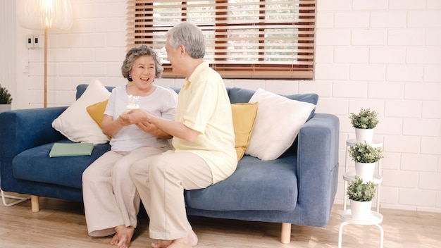 Torta mayor asiática de la tenencia del hombre de los pares que celebra el cumpleaños de la esposa en sala de estar en casa. pareja japonesa disfruta del momento del amor juntos en casa.