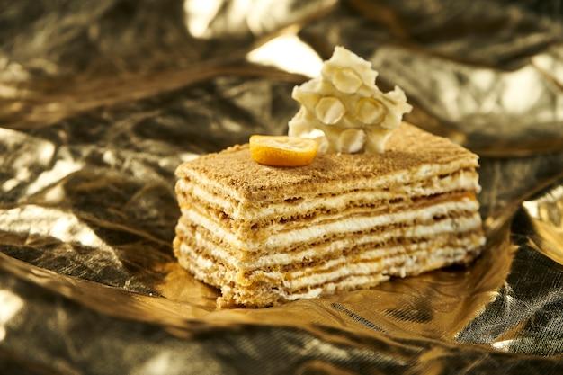 Torta de miel con capas y crema pastelera en mesa de oro. rebanada de delicioso pastel de medovik. de cerca. concepto de panadería sabrosa. enfoque selectivo