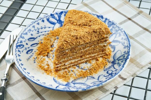 Torta de miel con capas y crema pastelera en plato de cerámica en mesa blanca. rebanada de delicioso pastel de medovik. de cerca. concepto de panadería sabrosa. enfoque selectivo