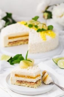 Torta de mousse tropical decorada, chips de coco, piña y rodaja de limón