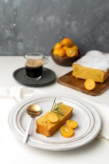 Torta de naranja servida decorada con kumquats frescos y romero, tabla de cortar de madera, café espresso