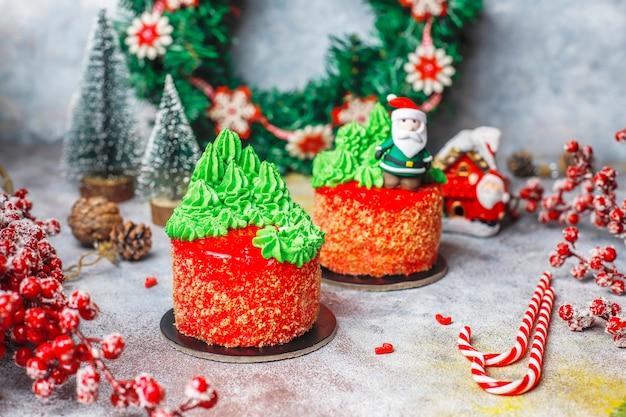 Torta navideña decorada con dulces figuras de árbol de navidad, santa claus y velas.