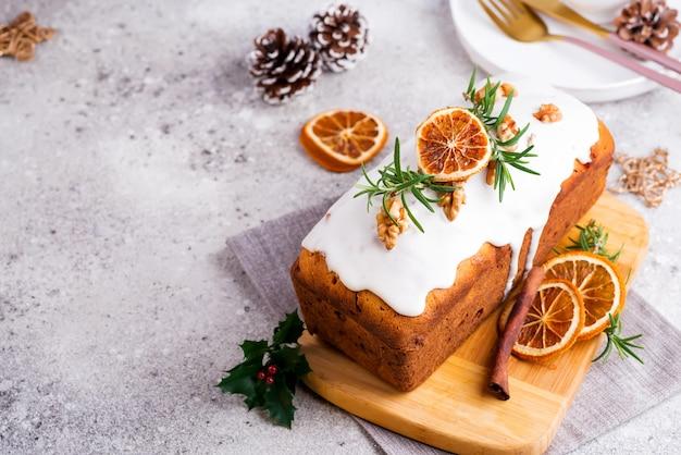 Torta de pan de fruta espolvoreada con glaseado, nueces y naranja seca sobre piedra. navidad y vacaciones de invierno