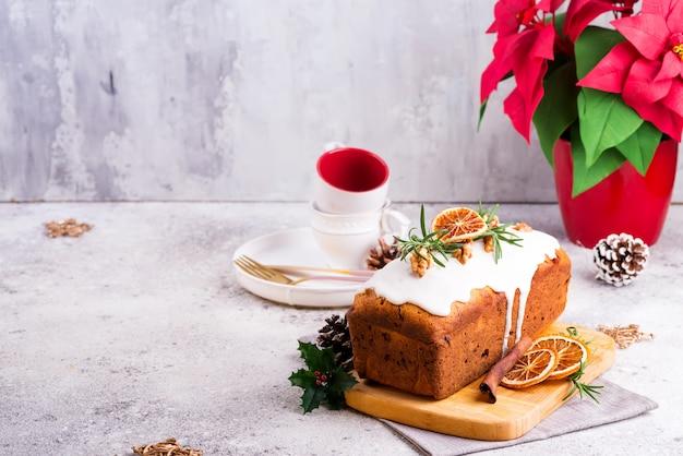 Torta de pan de fruta espolvoreada con glaseado, nueces y naranja seca sobre piedra. pastel casero de navidad e invierno