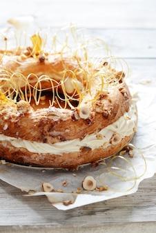 Torta paris-brest de la masa de natillas con natillas de aire, praliné y nueces en caramelo. postre francés pastelería.