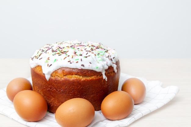 Torta de pascua y huevos de colores sobre fondo brillante