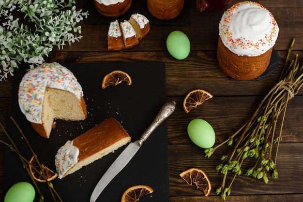 Torta de pascua y huevos coloridos en una tabla de madera. se puede utilizar como fondo.