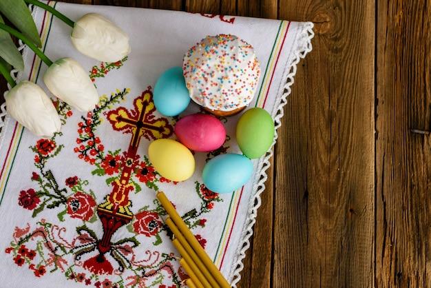 Torta de pascua y huevos coloridos en una tabla de madera.