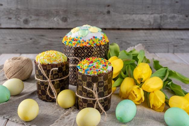 Torta de pascua, huevos pintados con los tulipanes en un viejo fondo rústico de madera.