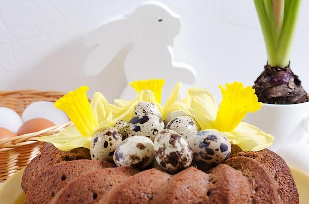 Torta de pascua con huevos teñidos en un nido, narcisos y jacintos en una taza sobre un fondo de madera rústico blanco
