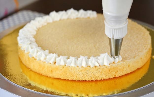 Torta en proceso en soporte en la tabla de madera, torta hecha en casa.