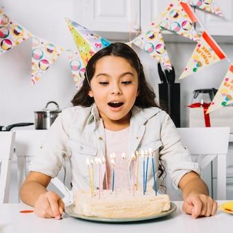 Torta que sopla sorprendida de la muchacha del cumpleaños con las velas iluminadas