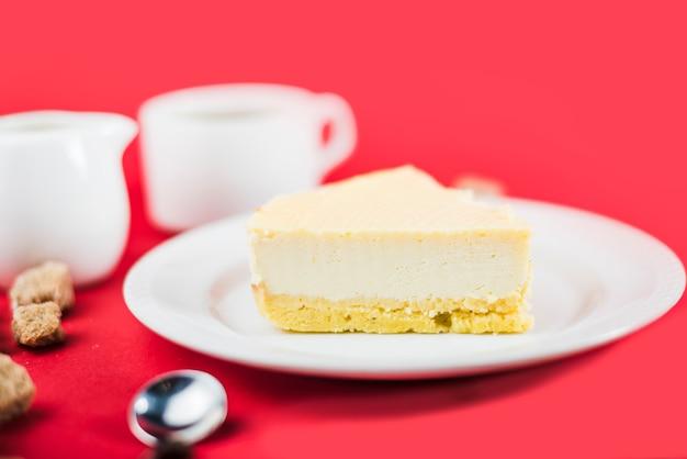 Torta de queso fresco en la placa blanca contra fondo rojo
