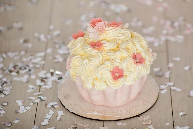 Torta rosa del primer cumpleaños con flores para la niña pequeña y decoraciones para romper la torta