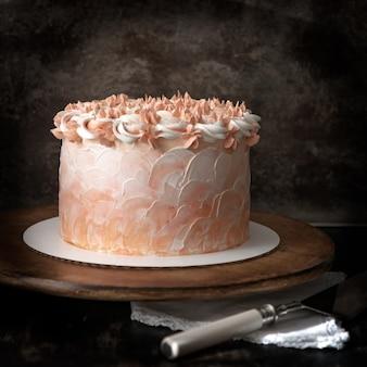 Torta sabrosa con glaseado de naranja en un soporte de madera y un cortador de pastel. fondo marrón