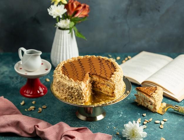 Torta de snickers cortada con maní y glaseado de caramelo