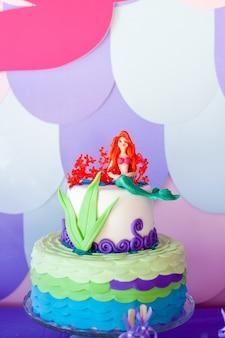 Torta temática de sirena con colas de colores brillantes, conchas y adornos de criaturas marinas