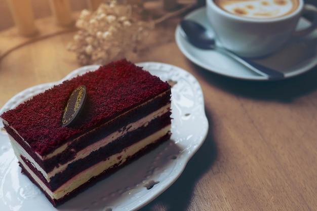 Torta de terciopelo rojo con taza de café caliente en la mesa de madera