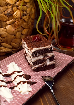 Torta de tiramisú en rodajas hecha de chocolate y esponja blanca. un trozo de postre sobre tablas de madera.