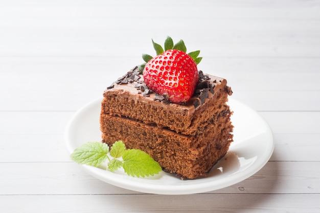 Torta de la trufa con el chocolate y fresas y menta en una tabla de madera blanca.