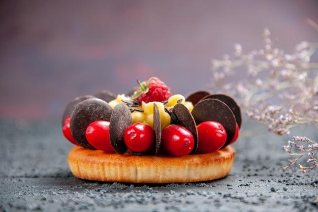 Torta de vista frontal con frambuesa de fruta de cornel y chocolate sobre fondo oscuro