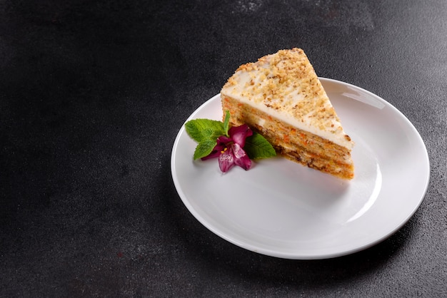 Torta de zanahoria deliciosa fresca con crema en un fondo oscuro. tarta de zanahoria con glaseado batido