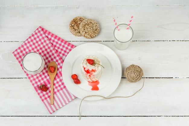 Tortas de arroz blanco de vista superior y fresas en un plato con mantel de cuadros rojos, cuchara de madera y productos lácteos en la superficie de la tabla de madera blanca. horizontal