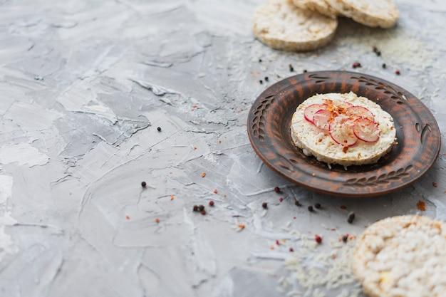 Tortas de arroz originales adornadas con un pequeño trozo de nabo y queso sobre fondo gris texturizado