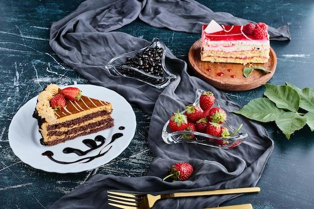 Tortas de caramelo y fresa acompañadas de frutas.