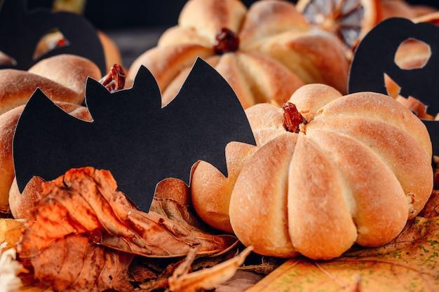 Tortas caseras en forma de calabaza de halloween con hojas de otoño sobre fondo oscuro