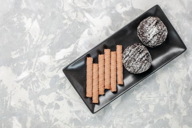 Tortas de chocolate de vista superior con galletas de pipa dulce dentro de la placa negra sobre superficie blanca