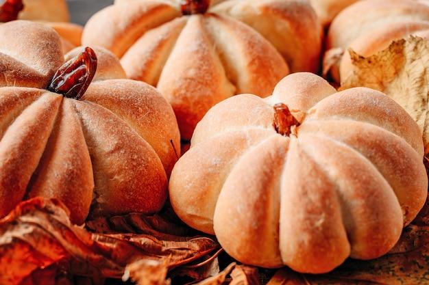 Las tortas hechas en casa en la forma de la calabaza con las hojas de otoño se cierran para arriba. concepto de dulces de halloween