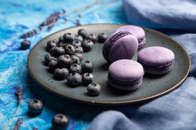 Tortas de macarons o macarrones púrpuras con arándanos en placa de cerámica sobre un fondo azul de hormigón.