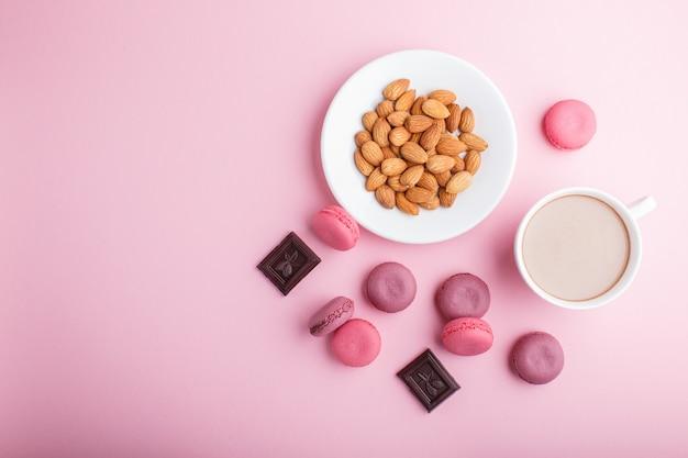 Tortas de macarrón o macarrón de color púrpura y rosa con taza de café y almendras en rosa pastel.