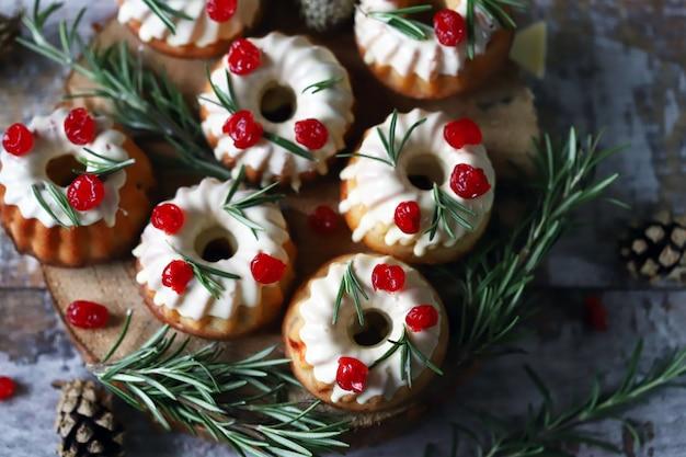 Tortas de navidad con glaseado blanco, frutos rojos y romero. decoración navideña. enfoque selectivo.